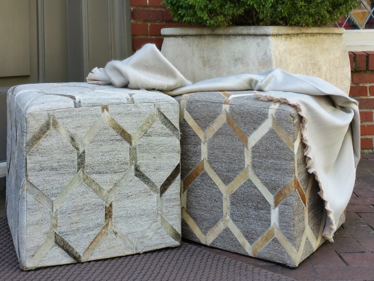 Cowhide-on-linen ottomans, $300 each, and alpaca blankets, $125, at at Paige Albright Orientals