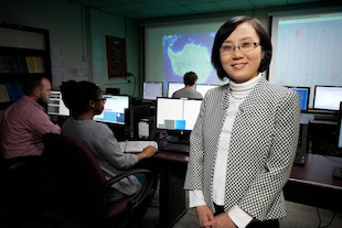 Eun-Suk Seo, UMD professor of physics and head of the UMD Cosmic Ray Physics Group, stands in the on-campus control room where her students and technicians help monitor Long Duration Balloon (LDB) missions when they are underway in Antarctica. Behind her are [L-R]: postdoctoral research associate Jacob Smith, lab assistant Oluchi Ofoha, and undergraduate researcher Nathan Anthony. Image Credit: Faye Levine/UMD (Click image to download hi-res version.)