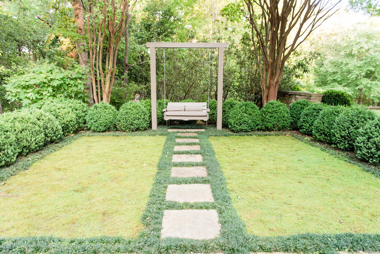 """""""The homeowners wanted a swing, so beside the family's 'pet cemetary,' we created a contemplative space surrounded with a boxwood hedge and mondo used to frame two rectangular moss rugs,"""" says John."""