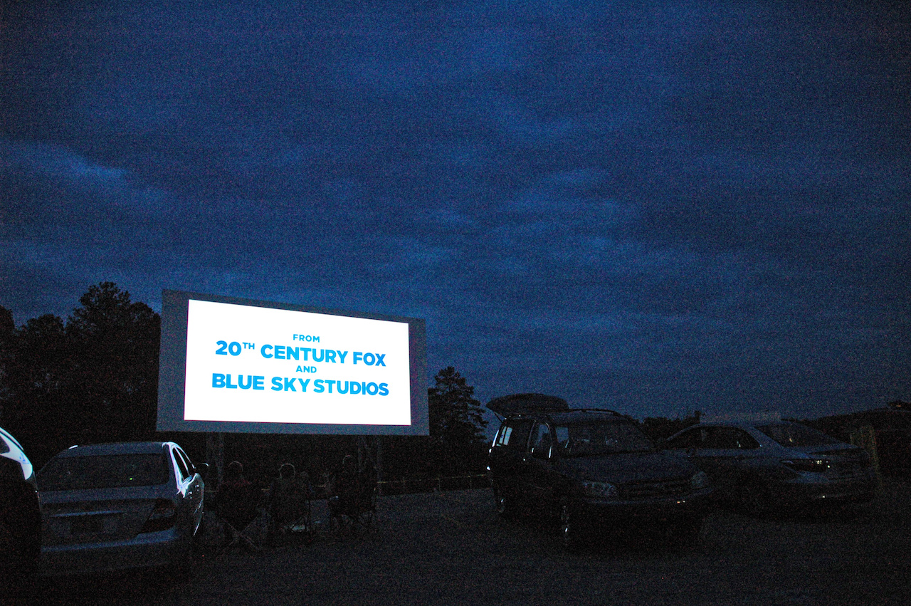 Audience members look onto the silver screen from car hatchbacks, front seats and camping chairs at the Coyote Drive-In & Canteen at dusk.