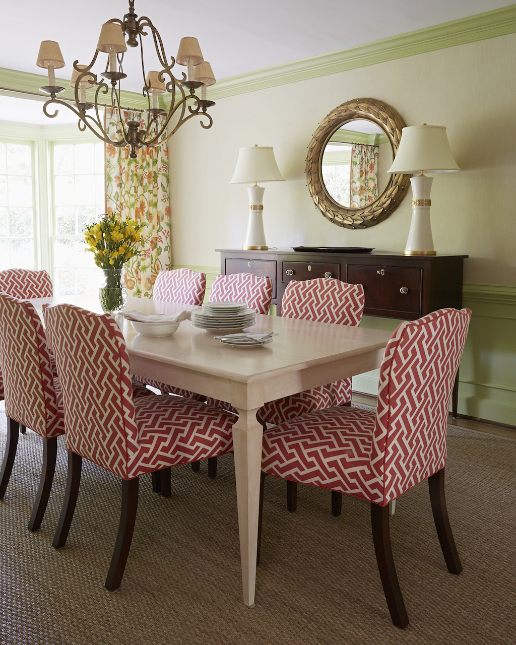 A sideboard by Kittinger and lamps from Mrs. Howardcomplement the red Quadrille fabric on dining room chairs.