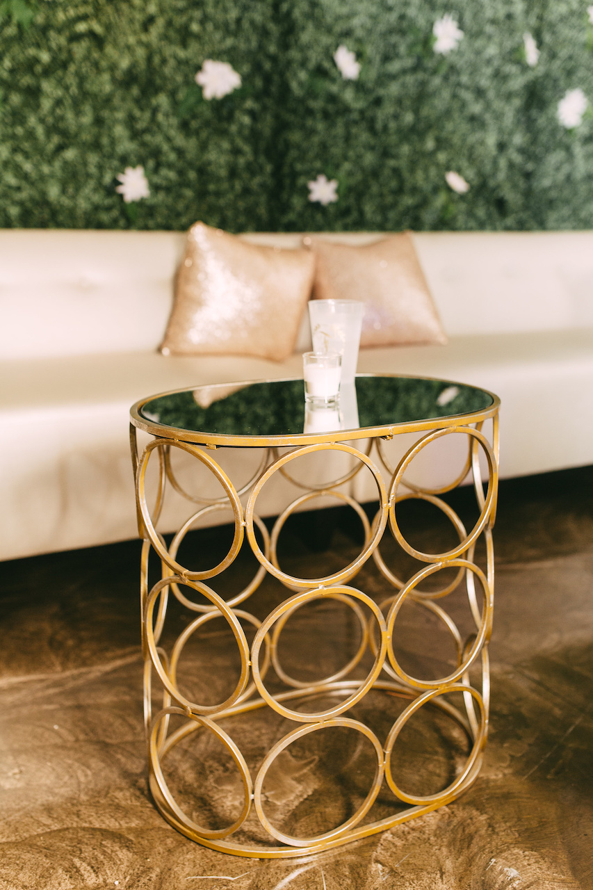 While the interior structure of the Cadre Building and its mass create its own stunning appeal, they added a boxwood wall, white leather sectionals and gold mirrored accent tables to give the room a more modern and chic allure.