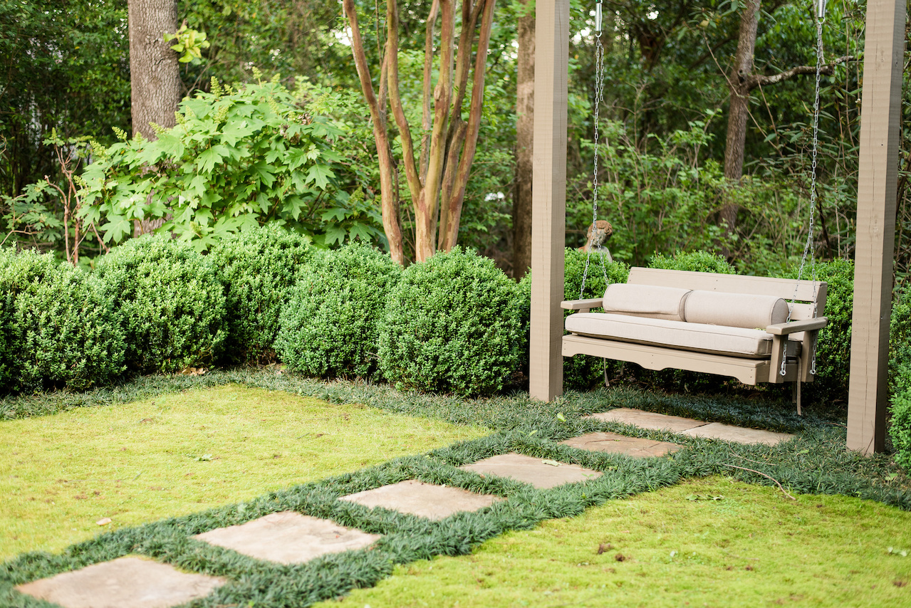 """""""A central stone paver walk divides the moss rugs leading to a swing looking back at the house,"""" says John. """"The moss was harvested from another area of the property and has thrived in its new setting."""""""
