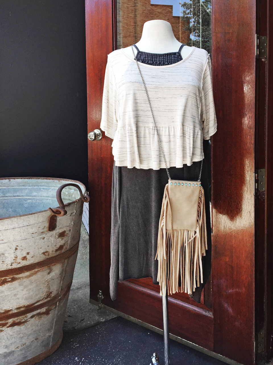 From Ambiance: black tank dress, $59; striped ruffle crop top, $39.99; leather fringe cross body, $139