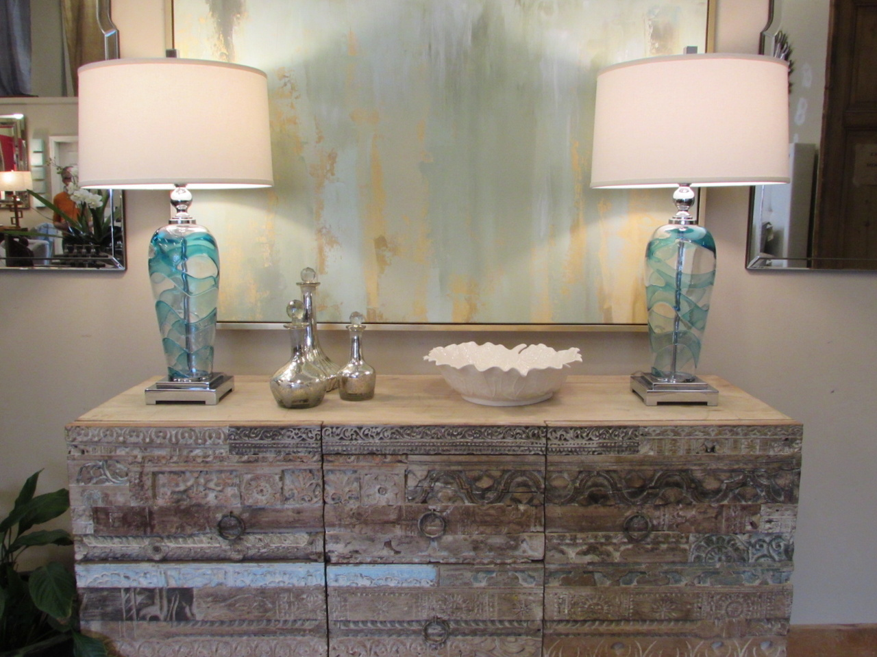 Carved chest of drawers $1,375; decorative glass decanters, $45-$75; abstract painting, $1,145; Andreas glass table lamps, $339 each; white stoneware leaf bowl, $69 – all found at Merridian Home Furnishings