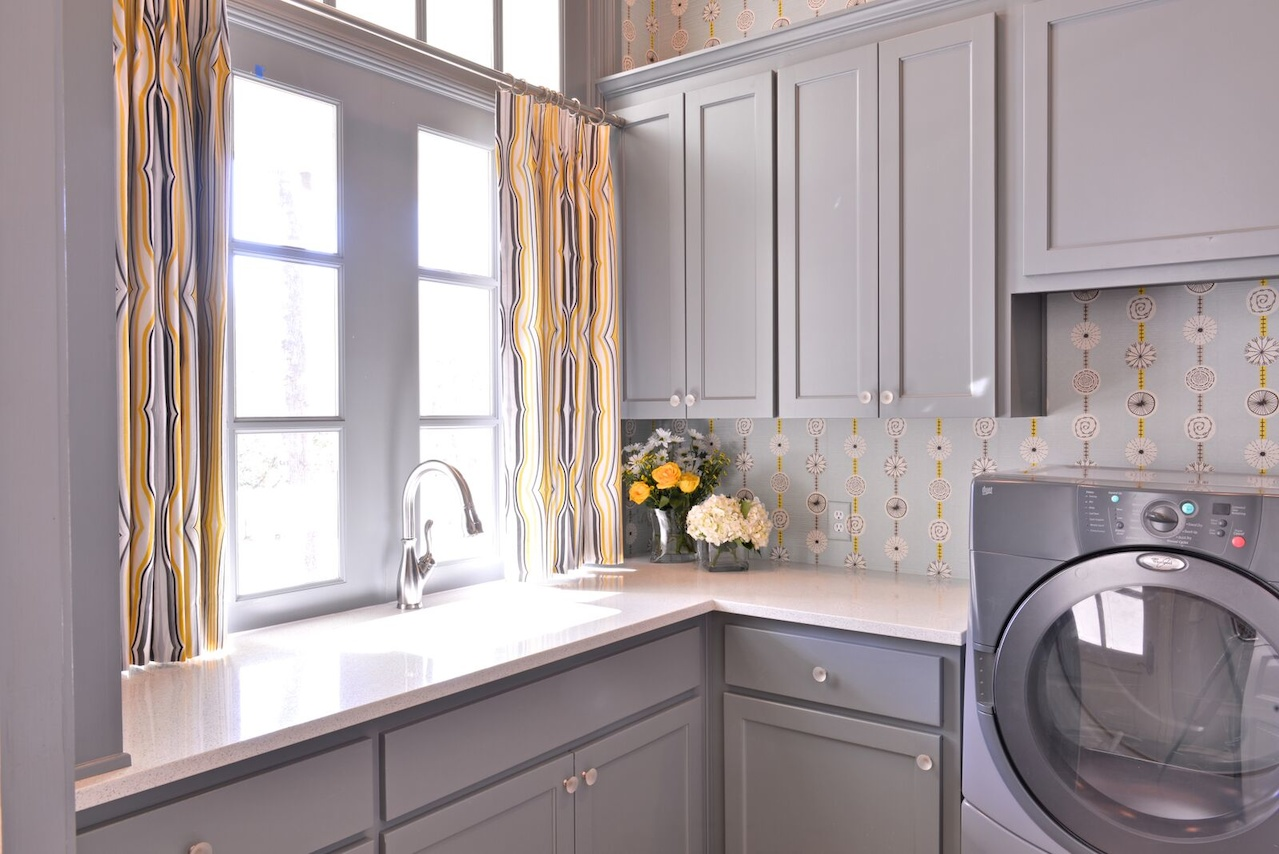 Even the laundry room stands out, thanks to drapery fabric from Duralee. Benjamin Moore's Shaker Gray covers the cabinetry.