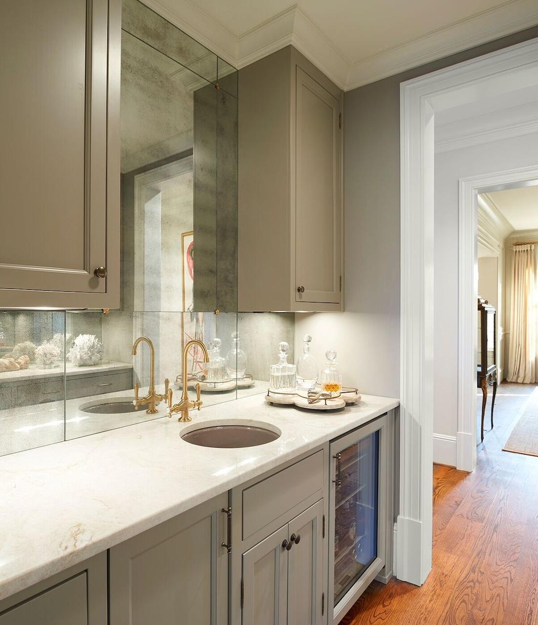 Antiqued-mirror walls line the butlers pantry, which has the convenience of a small sink for bar use.