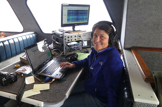 Marine biologist and bio-acoustician Shannon Rankin monitors acoustic data on a research ship. Credit: NOAA.