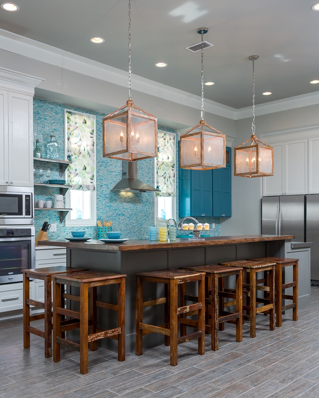 A teal cabinet and counter-to-ceiling glass tile in a similar hue provides a beachy vibe for this otherwise-neutral kitchen. The designer used her budget wisely to add upgrades such as two sinks, a built-in icemaker and the glass tiles.