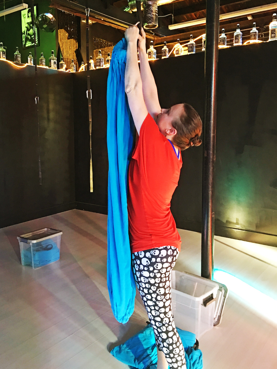 Aerial yoga instructor Christy Rose hangs up fabric slings in preparation for class.