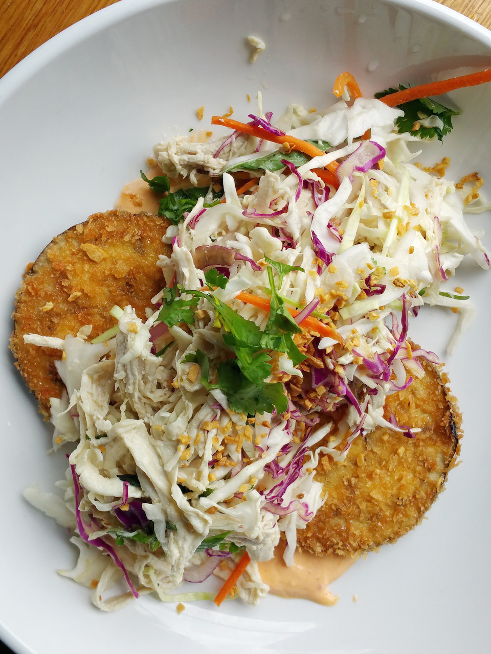 A refreshing chicken salad appetizer on crispy fried eggplant slices and topped with red cabbage, carrots, peanuts and cilantro