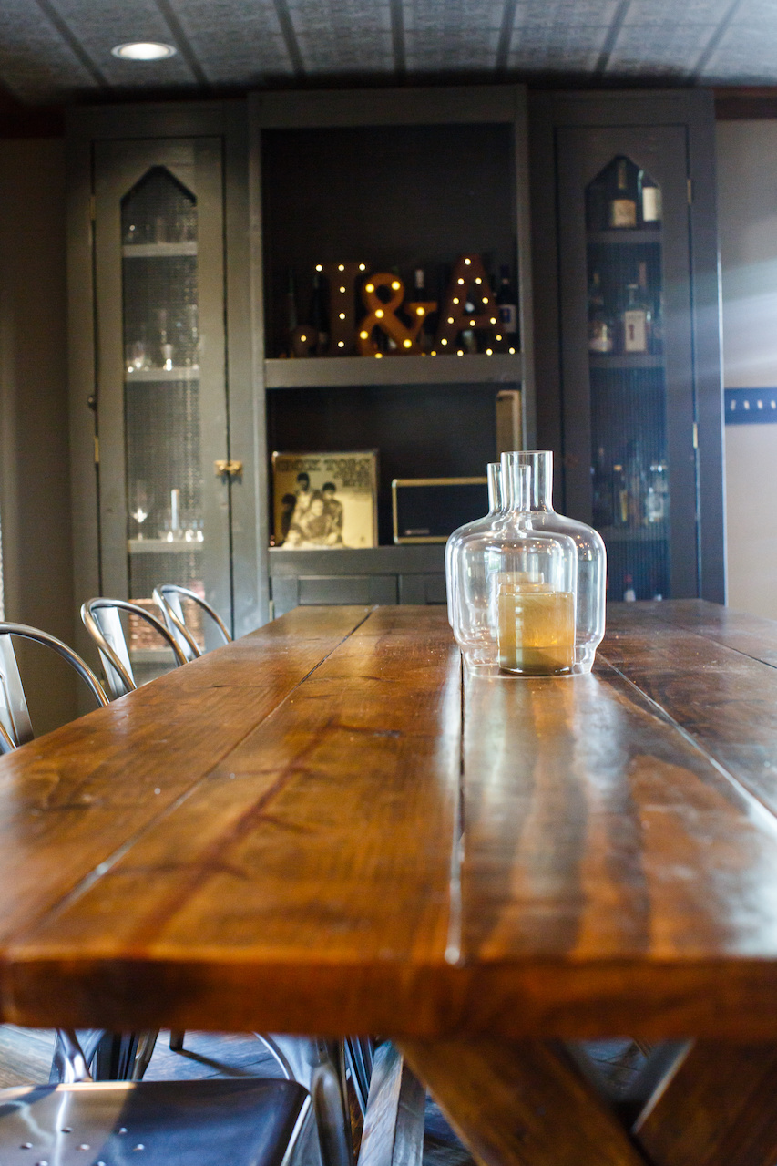 The opposite end of the dining room features a built-in bar area with clever open storage for liquor bottles and glassware.
