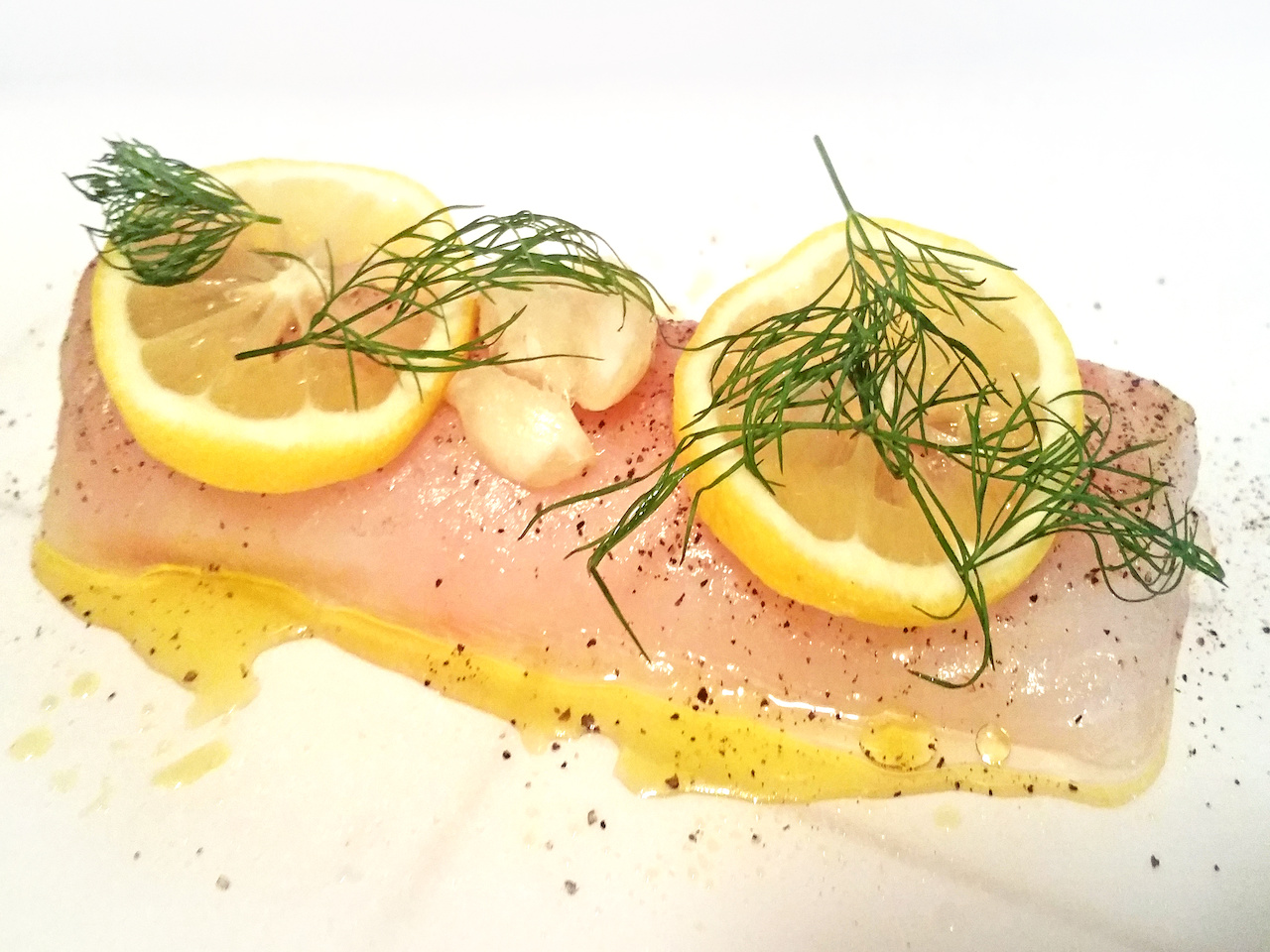 Here, we're preparing the cod atop parchment paper with olive oil, salt, pepper, fresh dill, garlic and lemons before we close up the parchment pouches. The delicate cod will steam inside the pouches for a truly aromatic dish.