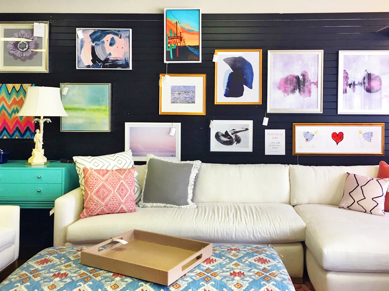 Paintings, photographs, and prints line the shop walls at Frugal Home Finds.