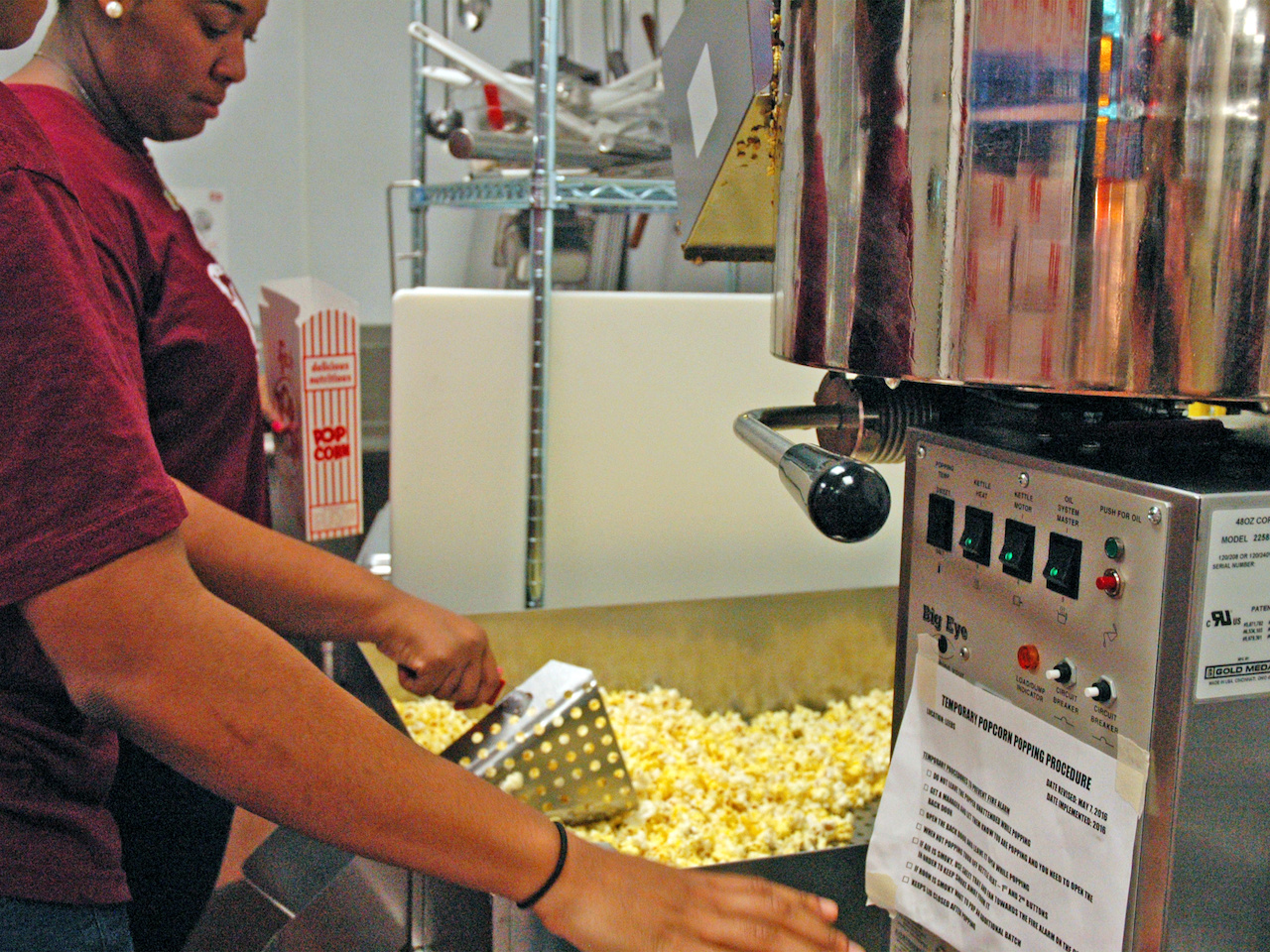 Employees scoop buttery popcorn into boxes.