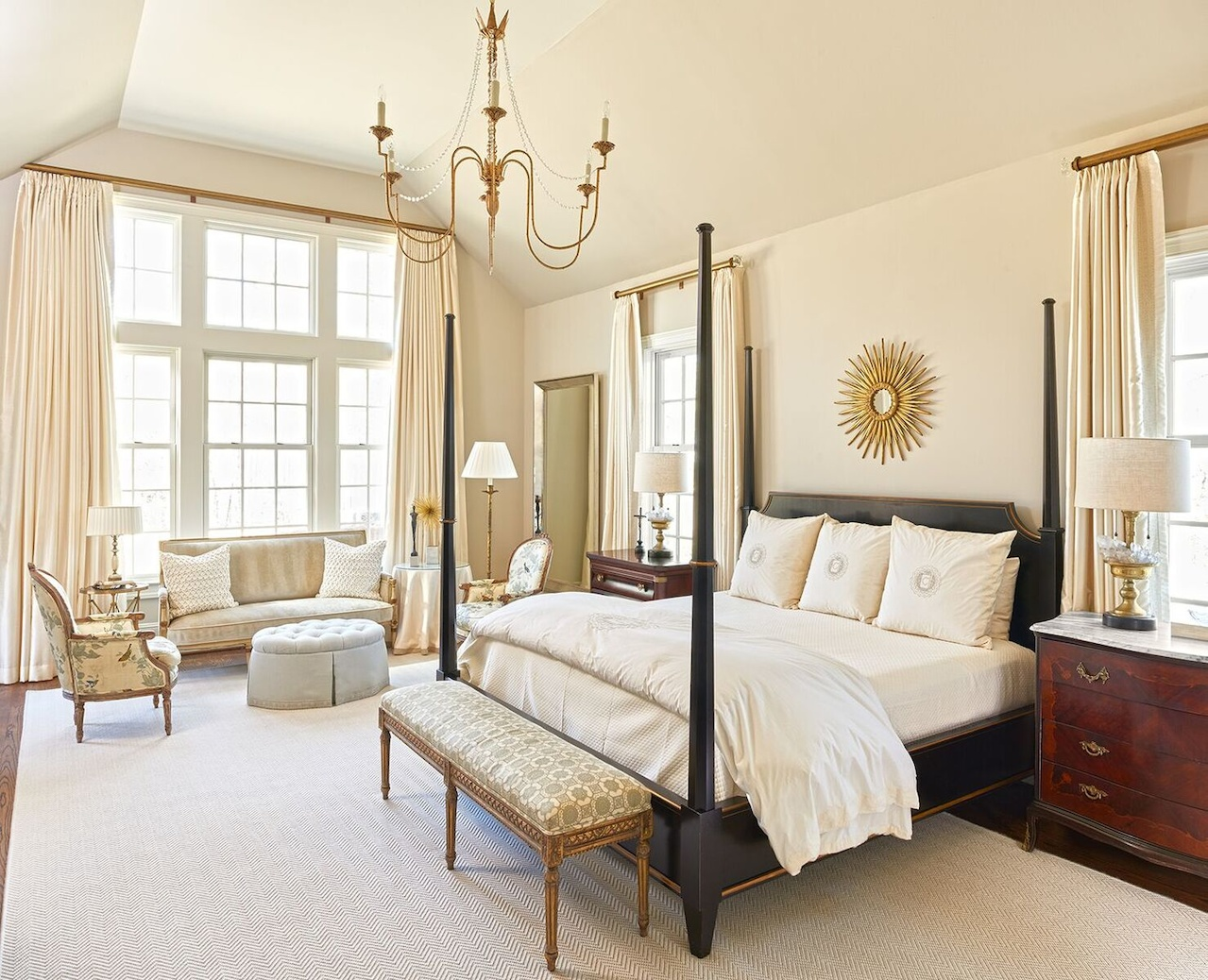 Antiques fill the master bedroom, reminiscent of an upscale hotel suite. The designer painted walls a tinted version of Benjamin Moore's Revere Pewter.