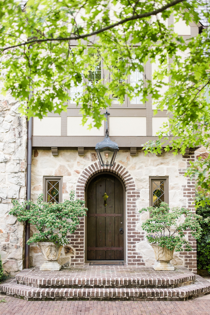 """""""A brick coining detail was added to the arched front door,"""" says John of one way that they merged the new landscape architecture into the existing home."""
