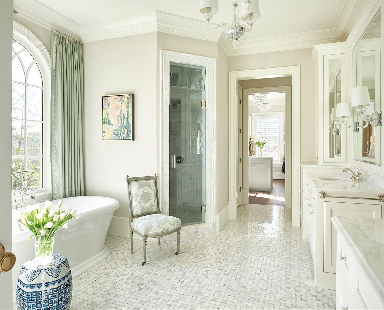 Luxurious window treatments—made from Duralee fabrics—soften the free-standing tub. Soft shades of green elevate the bathroom from a typical all-white scenario.