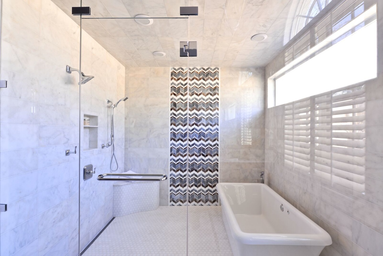 Chevron-patterned tiles are a striking focal point in the wet room, with its free-standing tub and multiple shower heads.
