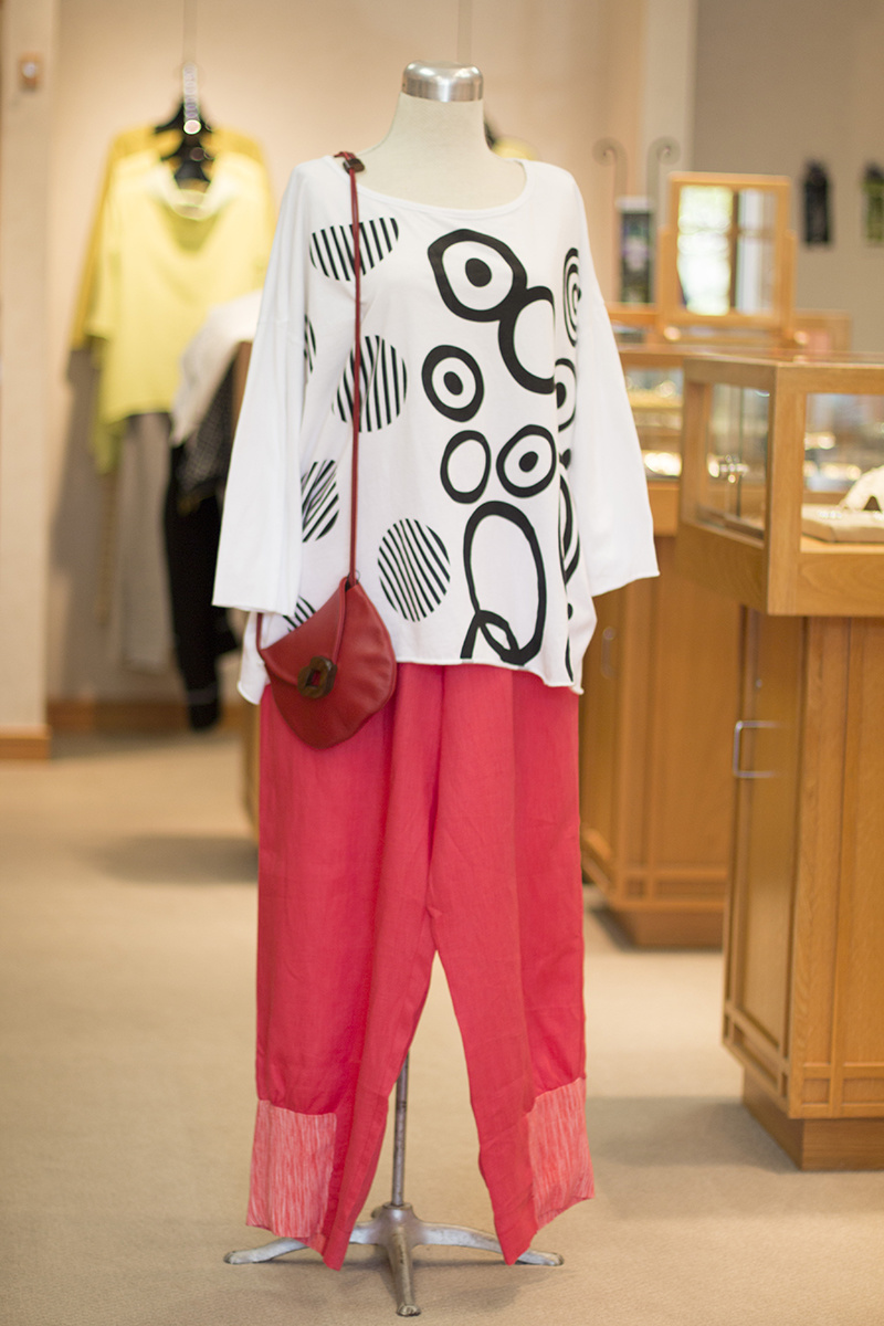 From Timna: Black and white screen-printed, graphic cotton top, $120; Corral linen pants with detailed hemline, $284; Red leather Lips bag with hand-carved walnut closure, $148