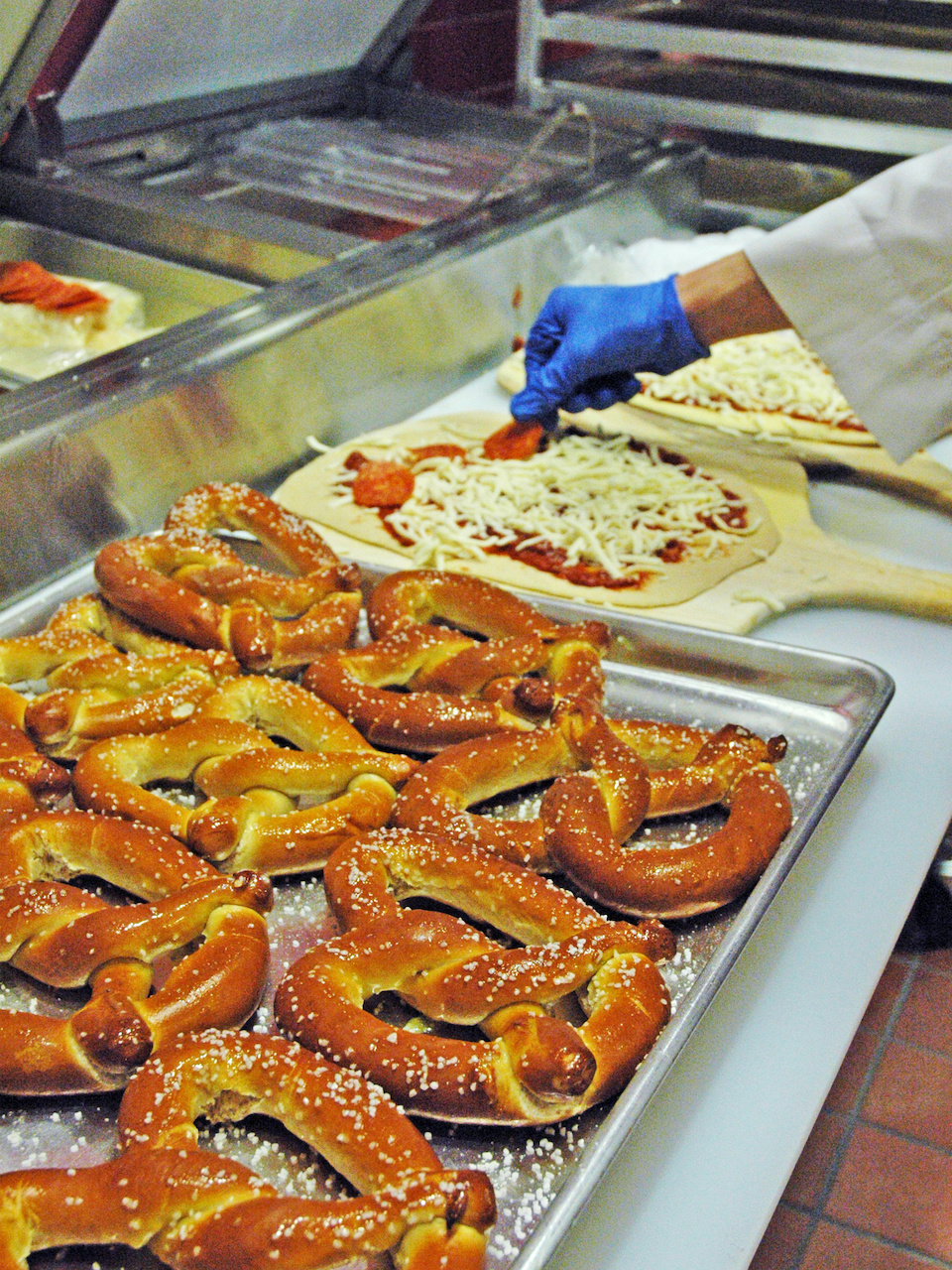 In the Canteen kitchen, pizza and pretzels are prepared for hungry moviegoers.