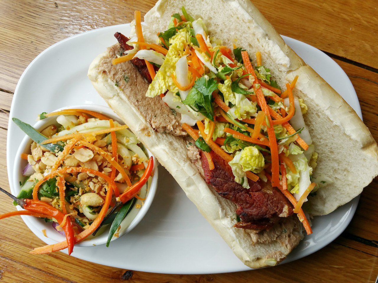 Pork belly bahn mi on crispy bread with bright crunchy veggies