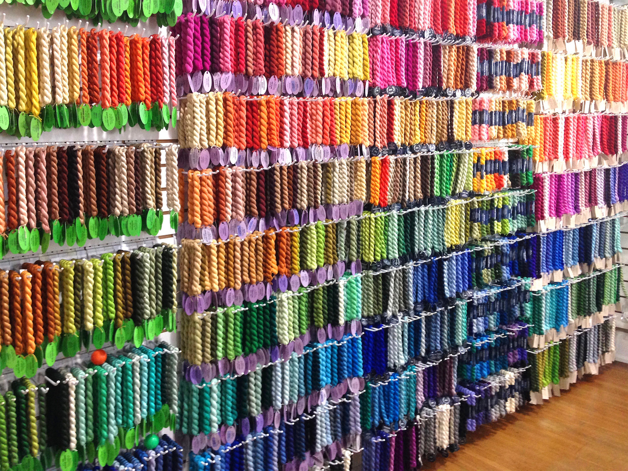 Rows and rows of brightly colored thread lines the walls of this needlepoint haven.
