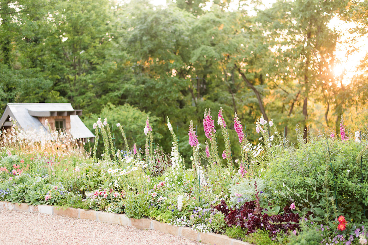 The flower wall is hemmed in by a stone wall, adjacent to the herb garden and charming gardening house.