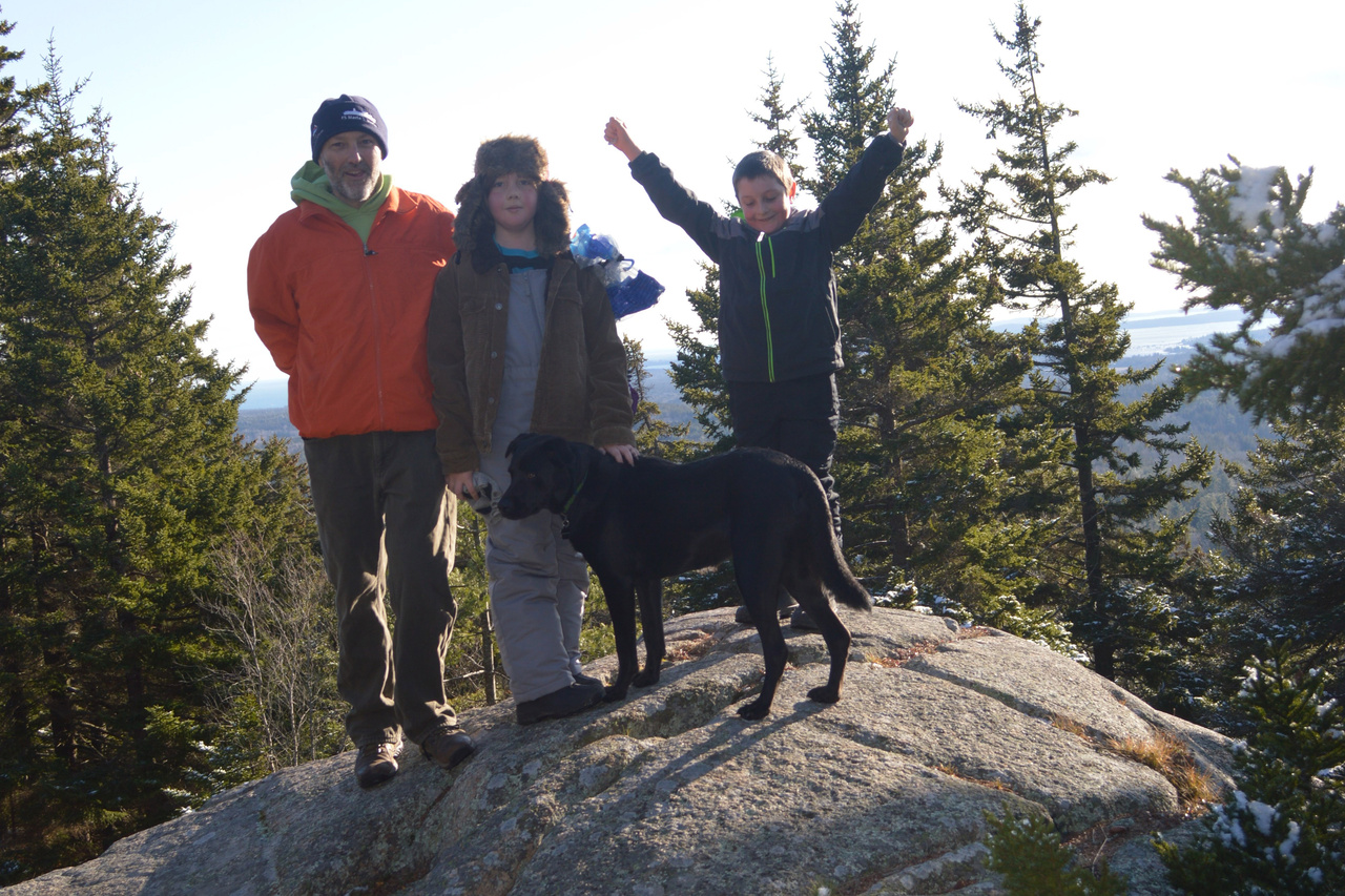 Harvey Walsh and his children stand atop a large boulder while hiking on Beech Mountain in Acadia National Park, Maine