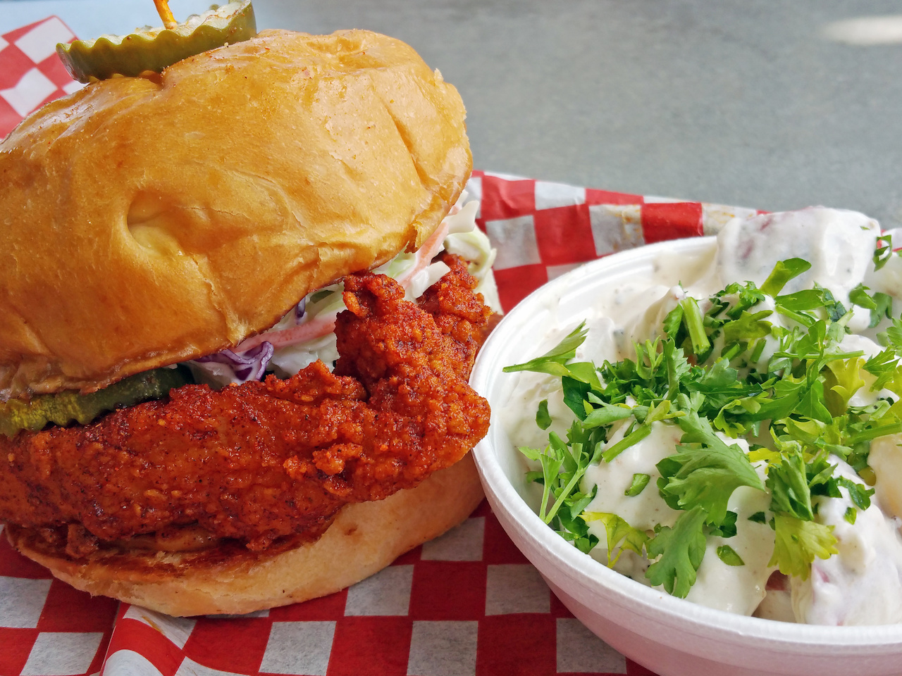 The Hattie B's hot chicken mouthwatering sandwich pairs perfectly with the house potato salad.