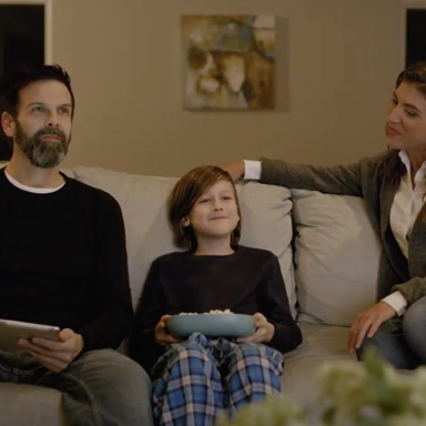 Man, child, and woman on couch together