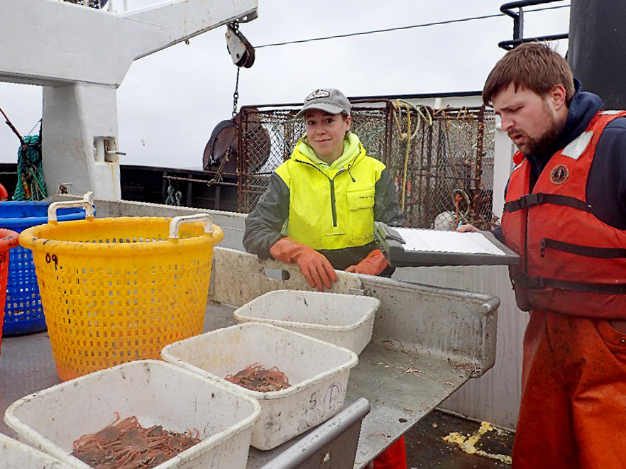 Biologists Julia Dissen (Alaska Department of Fish and Game) and Charlie Heller (Bering Sea Fisheries Research Foundation) sort and measure the Tanner crab catch.
