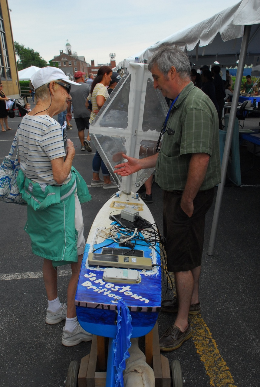Manning talks wioth a visoto to the Woods Hole Science Stroll standing next to a miniboat. l.JPG