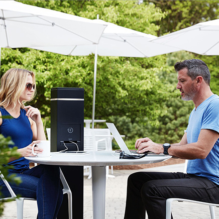 Woman and man sitting hear a mobile charging device at an outside patio area