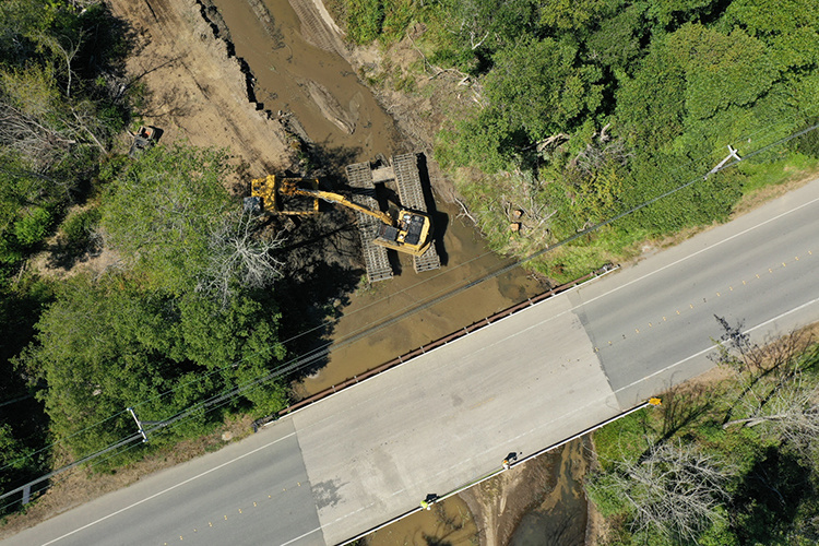 Aerial view of construction equipment in a river, with a road running nearby