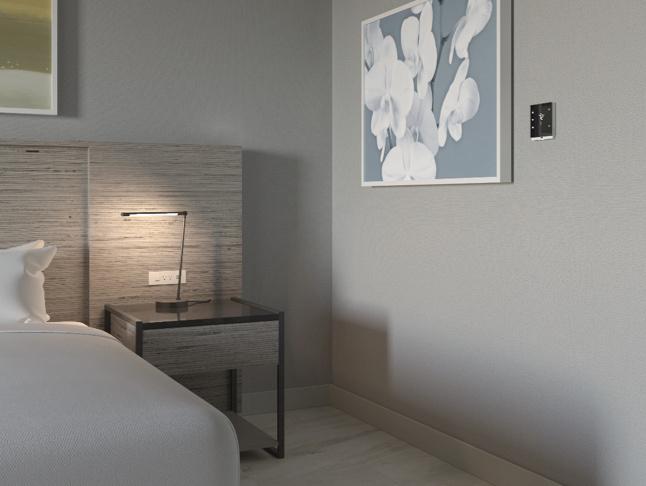 Corner of hotel room with headboard and smart lighting controls