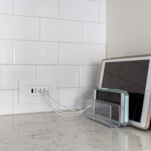 Tablet and phone charging on kitchen counter by four usb ports