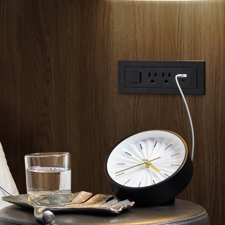 black outlets and USB receptacles built into wooden wall above table with analog clock and glass of water