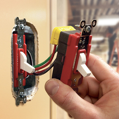 Contractor hand installing red PlugTail switch
