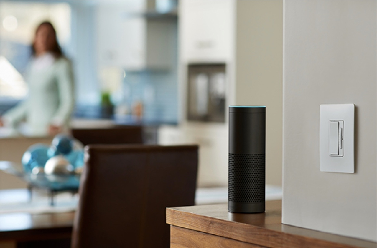 Amazon Alexa on wooden ledge next to white Legrand smart dimmer on beige wall with woman in the background