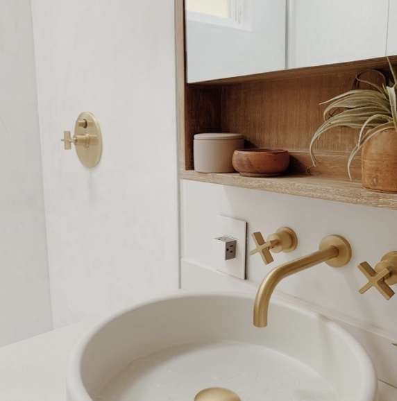 White pop out outlet in white bathroom with brass accents