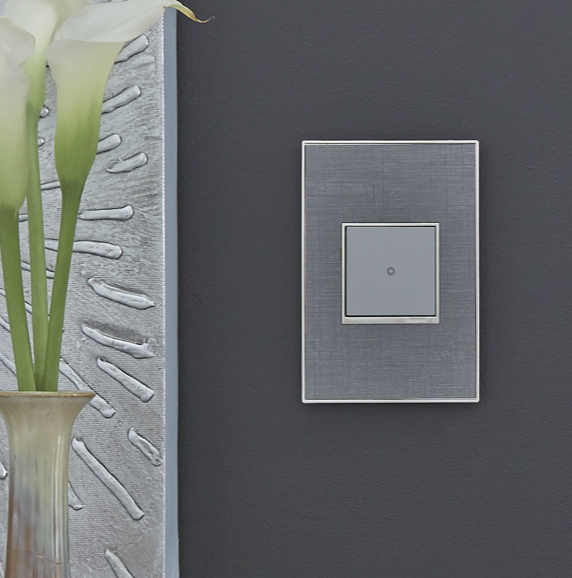 adorne touch switch with textured wall plate against dark gray wall