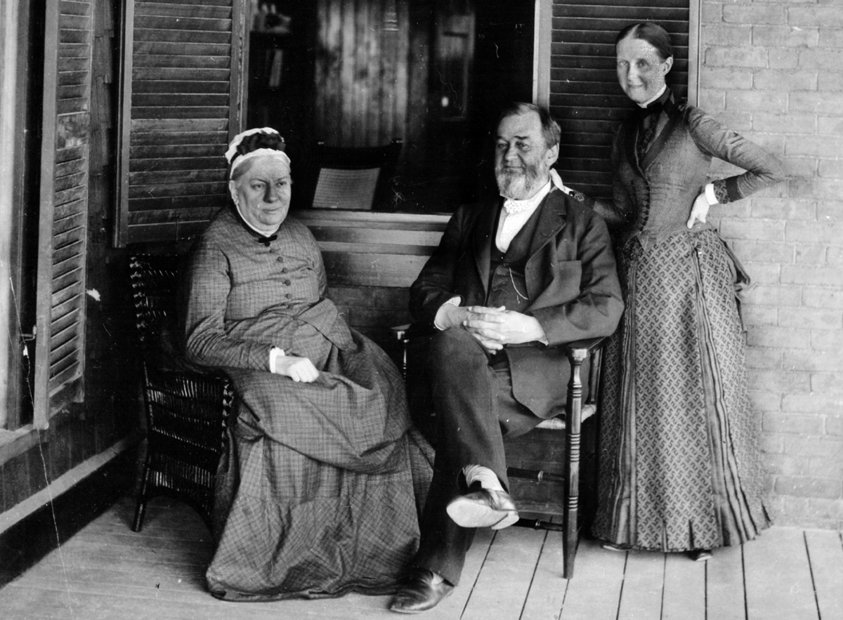 1893 photo of Spencer Baird with his wife and daughter on porch of residence