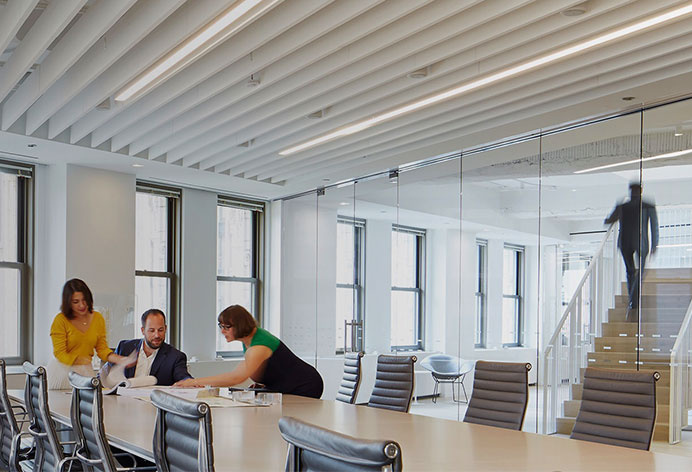 Professionals huddled around conference table in modern commercial office space