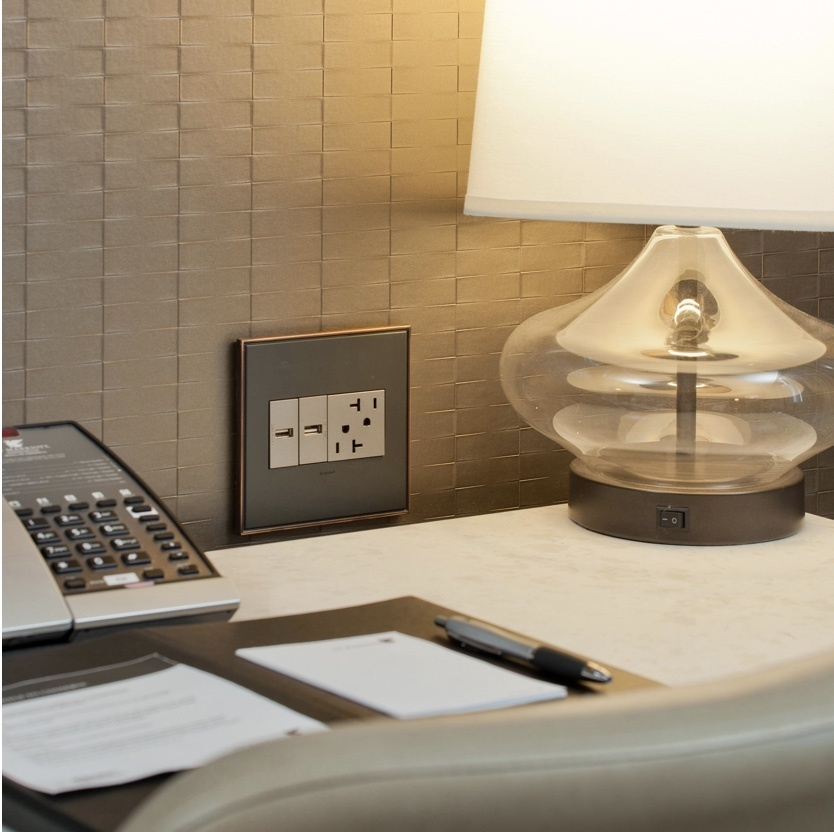 adorne furniture power center in wall above hotel desk