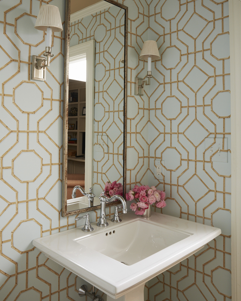 Cowtan & Tout's trellis wallpaper adds dimension and architectural interest to the powder room.