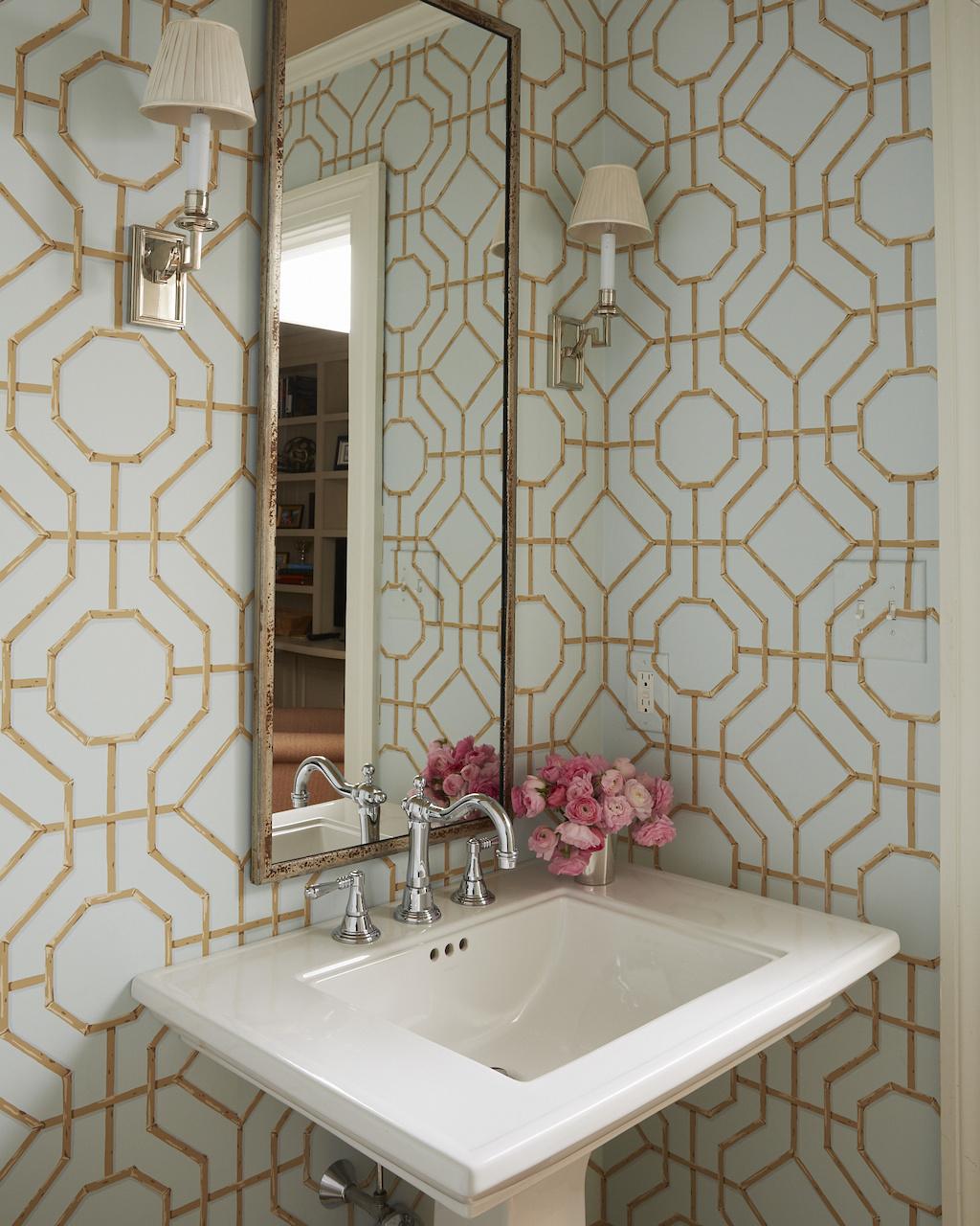 Cowtan & Tout's trellis wallpaper adds dimensionandarchitectural interest to the powder room.