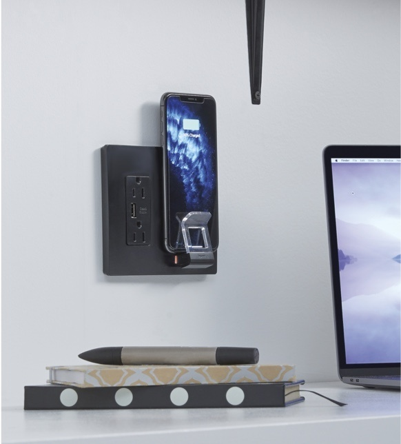 Black radiant wireless charging against white wall charging phone in office