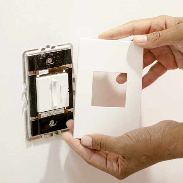 Installation of adorne Collection screwless wall plate in white over adorne whisper dimmer