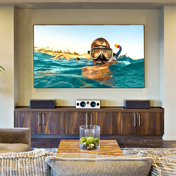Living room with large flatscreen television mounted on the wall above a large wooden cabinet with 3 sound bars on top